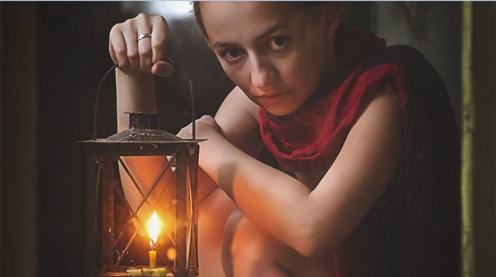 donna spaventata che regge una lanterna in mano